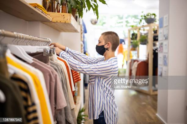 saleswoman with face mask arranging clothes in store - womenswear stock pictures, royalty-free photos & images