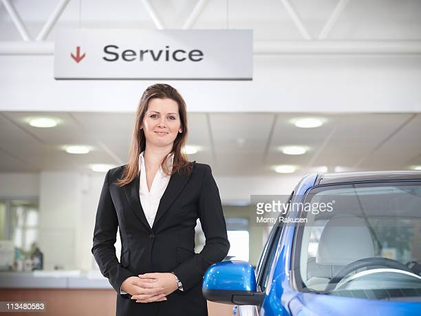 Saleswoman with hands together under large service sign with car in car dealership