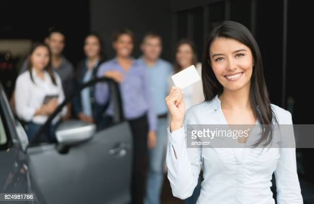 Saleswoman working at a car dealership and holding a business card
