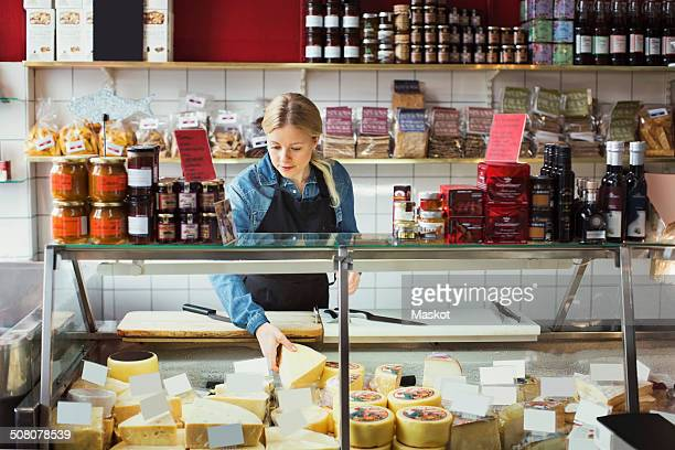 Saleswoman working at display cabinet in supermarket