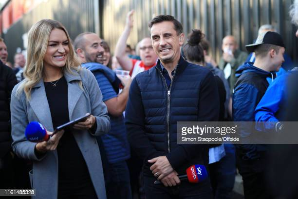 Salford coowner Gary Neville gestures alongside Sky Sports television copresenter Laura Woods before the Carabao Cup First Round match between...