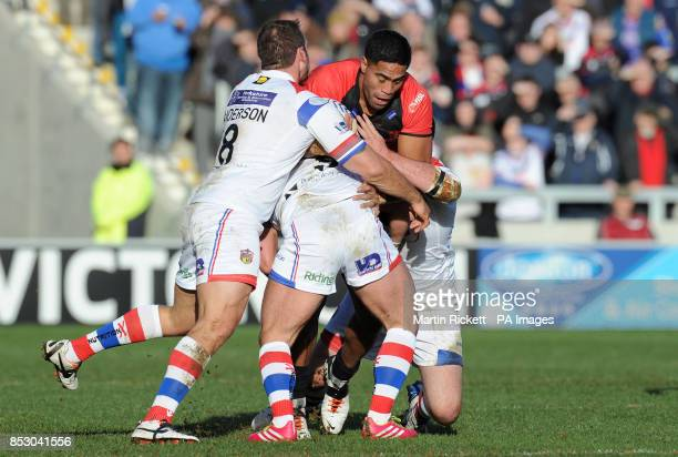 Salford Red Devils' Lama Tasi is tackled by Wakefield Trinity Wildcats' Scott Anderson Paul McShane and Daniel Smith during the Super League match at...