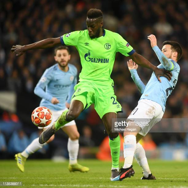 Salif Sane of FC Schalke 04 controls the ball as David Silva of Manchester City looks on during the UEFA Champions League Round of 16 Second Leg...