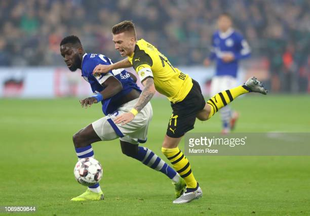Salif Sane of FC Schalke 04 is challenged by Marco Reus of Borussia Dortmund during the Bundesliga match between FC Schalke 04 and Borussia Dortmund...