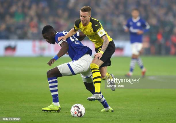 Salif Sane of FC Schalke 04 is challenged by Marco Reus of Borussia Dortmund during the Bundesliga match between FC Schalke 04 and Borussia Dortmund...