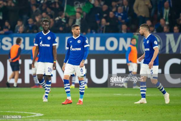 Salif Sane of FC Schalke 04 Omar Mascarell of FC Schalke 04 and Matija Nastasic of FC Schalke 04 look dejected during the DFB Cup match between FC...