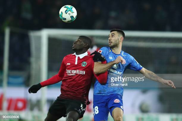 Salif Sane of Hannover and Gerrit Holtmann of Mainz compete for the ball during the Bundesliga match between Hannover 96 and 1 FSV Mainz 05 at...