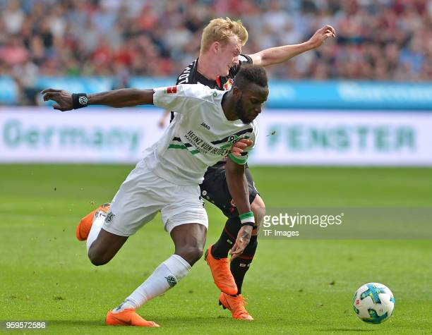 Salif Sane of Hannover and Julian Brandt of Leverkusen battle for the ball during the Bundesliga match between Bayer 04 Leverkusen and Hannover 96 at...