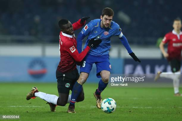 Salif Sane of Hannover and Stefan Bell of Mainz compete for the ball during the Bundesliga match between Hannover 96 and 1 FSV Mainz 05 at HDIArena...