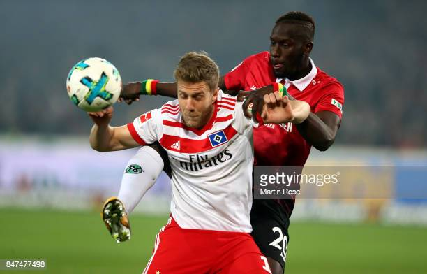 Salif Sane of Hannover and Sven Schipplock of Hamburg battle for the ball during the Bundesliga match between Hannover 96 and Hamburger SV at...