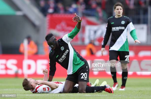 Salif Sane of Hannover calls for the Koeln team doctors after hitting Simon Terodde of Koeln during the Bundesliga match between 1 FC Koeln and...