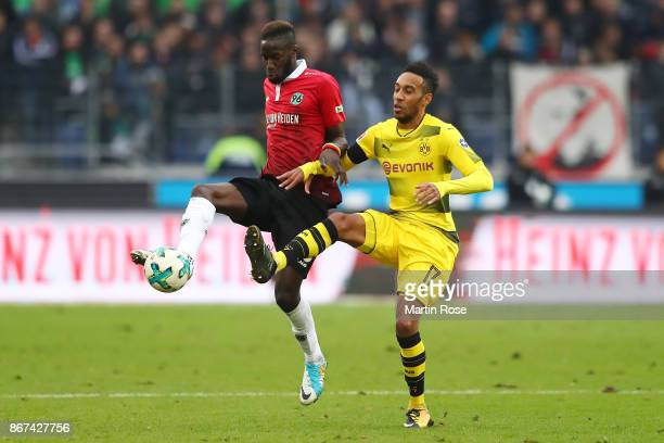 Salif Sane of Hannover fights for the ball with PierreEmerick Aubameyang of Dortmund during the Bundesliga match between Hannover 96 and Borussia...
