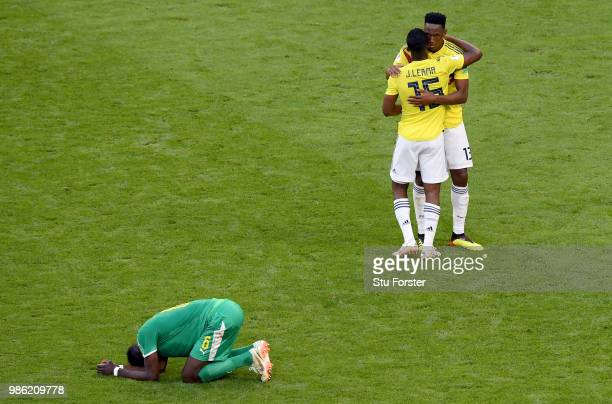 Salif Sane of Senegal looks dejected as Jefferson Lerma of Colombia and Yerry Mina of Colombia celebrate following their sides victory in the 2018...