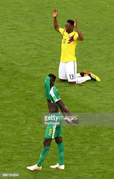 Salif Sane of Senegal looks dejected as Yerry Mina of Colombia celebrates following his sides victory in the 2018 FIFA World Cup Russia group H match...