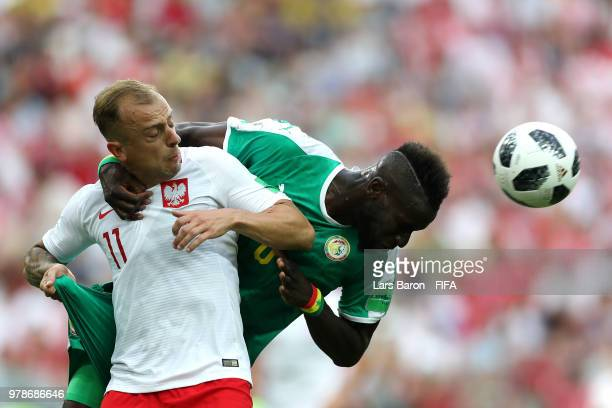 Salif Sane of Senegal wins a header over Kamil Grosicki of Poland during the 2018 FIFA World Cup Russia group H match between Poland and Senegal at...