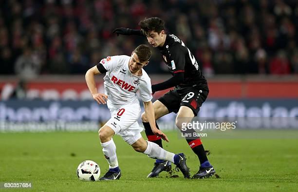 Salih Oezcan of Koeln is challenged by Kai Havertz of Bayer Leverkusen during the Bundesliga match between 1 FC Koeln and Bayer 04 Leverkusen at...