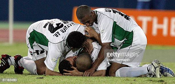 Salih Sadir of Iraq is hugged by team mates after scoring the final goal in Iraq's 42 victory over Portugal in the men's football preliminary match...