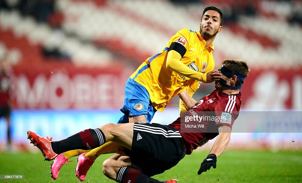 Salim Khelifi (top) of Braunschweig and Laszlo Sepsi of Nuernberg collide during the Second Bundesliga match between 1. FC Nuernberg and Eintracht Braunschweig at Grundig-Stadion on November 23, 2015 in Nuremberg, Germany.