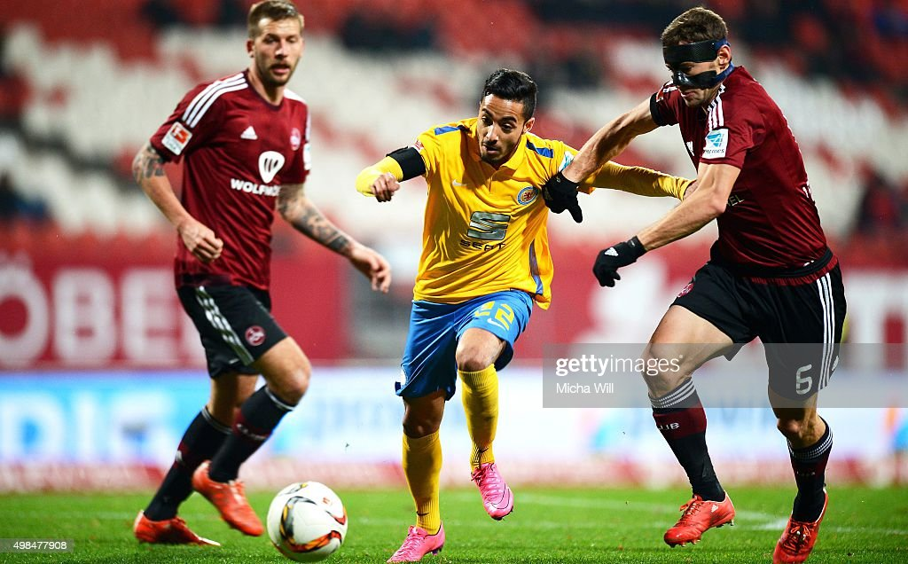 Salim Khelifi (C) of Braunschweig and Laszlo Sepsi (R) of Nuernberg compete for the ball during the Second Bundesliga match between 1. FC Nuernberg and Eintracht Braunschweig at Grundig-Stadion on November 23, 2015 in Nuremberg, Germany.