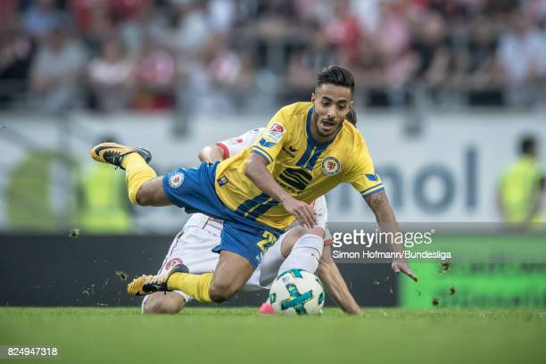 Salim Khelifi of Braunschweig is tackled by Niko Giesselmann of Duesseldorf during the the Second Bundesliga match between Fortuna Duesseldorf and...