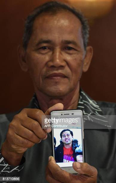 Salim Sarmo the father of Mohamad Ali Mohamad Salim who was killed in the shootdown of Malaysia Airlines flight MH17 displays a photograph of his...