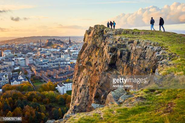 salisbury crags, holyrood park with edinburgh city the in background at sunset - scotland imagens e fotografias de stock