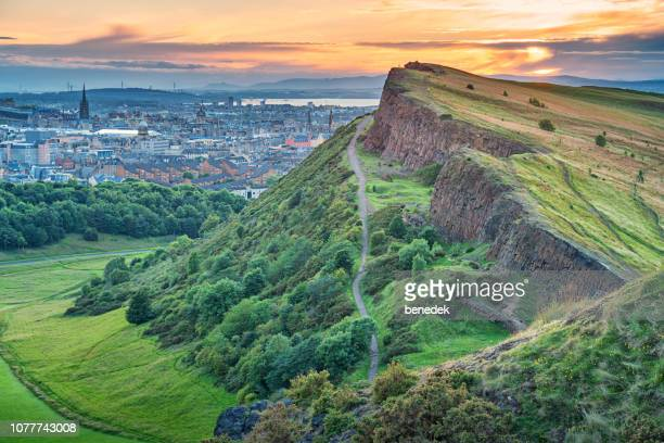 salisbury crags in holyrood park and downtown edinburgh scotland - edinburgh scotland stock pictures, royalty-free photos & images