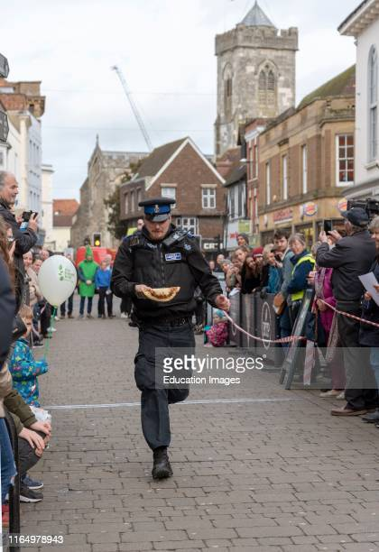 Salisbury Wiltshire UK 5th Competitors competing in the annual pancake race on High Street Salisbury The event is organized by St Thomass Church and...