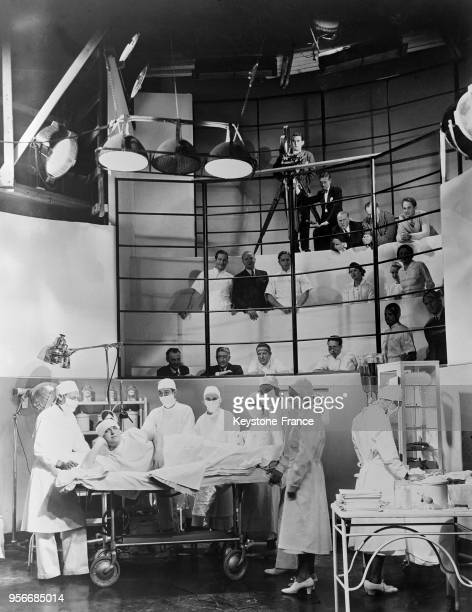 Salle d'opérations reconstituée pour un film de la MetroGoldwynMayer on remarque la présence du cameraman et l'attitude singulière d'un assistant...