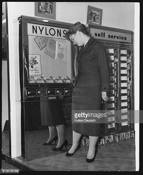 Sally Eves tries on a pair of nylon stockings bought from a machine at the first International Automatic Vending Machine Fair at the Royal...