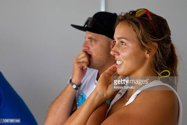 Sally Fitzgibbons of Australia watches the action replays on the big screen in the competitors area alongside Jake Patterson of Australia during the...