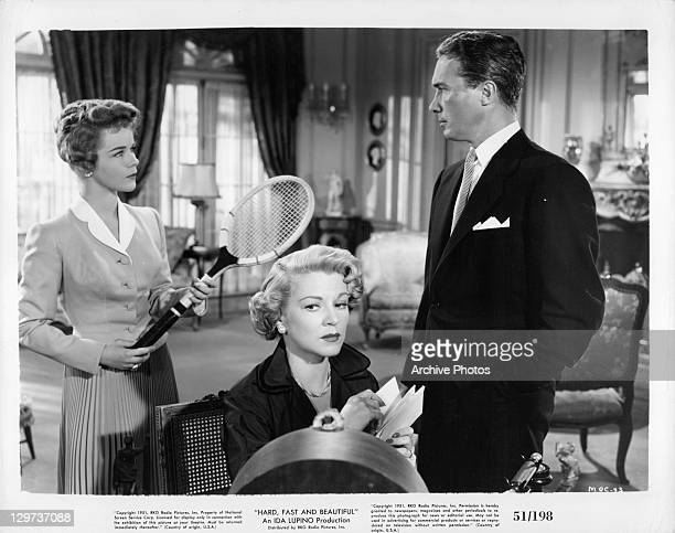Sally Forrest holding tennis racket behind Claire Trevor while Carleton G Young stands next to them in a scene from the film 'Hard Fast And...