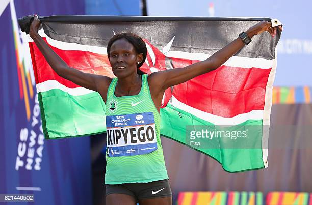Sally Kipyego of Kenya secondplace finisher celebrates with the Kenyan flag after the Professional Women's Division during the 2016 TCS New York City...