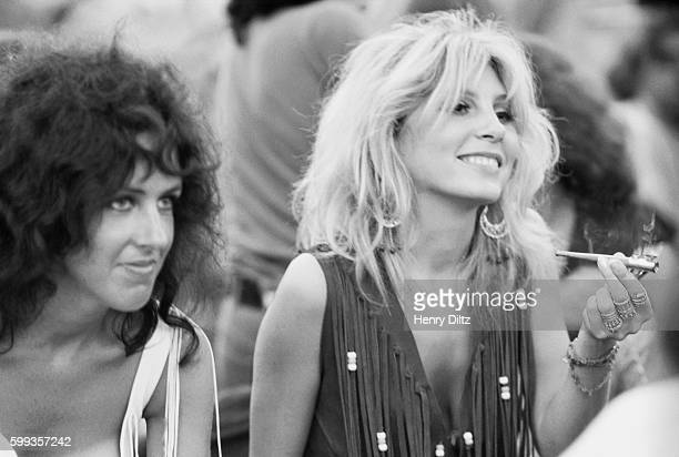 Sally Mann holding a joint sits next to Grace Slick at the free Woodstock Music and Art Fair | Location Near Bethel New York USA