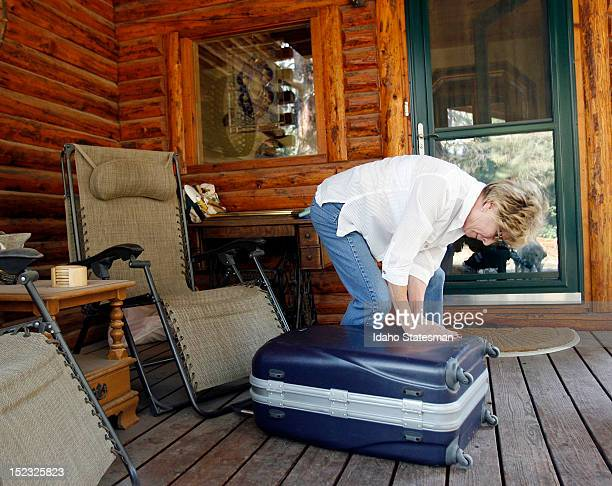 Sally Murray tries to close a suitcase stuffed with personal belongings on the front porch of the home she shares with her husband Rick while...