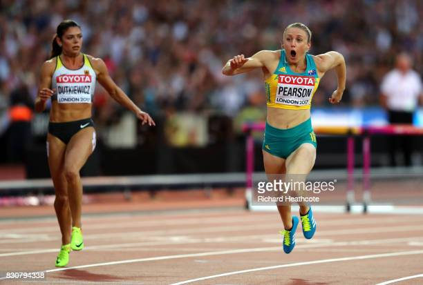 Sally Pearson of Australia and Pamela Dutkiewicz of Germany cross the finishline in the Women's 100 metres hurdles final during day nine of the 16th...