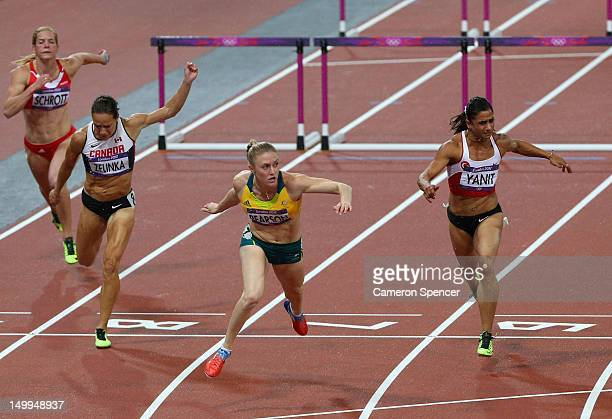 Sally Pearson of Australia crosses the finish line ahead of Jessica Zelinka of Canada and Nevin Yanit of Turkey to win gold in the Women's 100m...