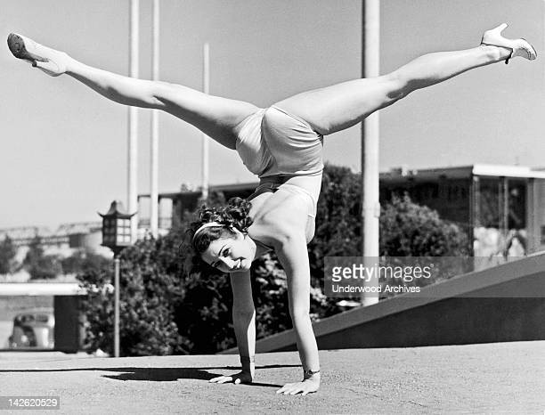 Sally Rand combines a hand stand with the splits at the Golden Gate International Exhibition on Treasure Island San Francisco California 1939