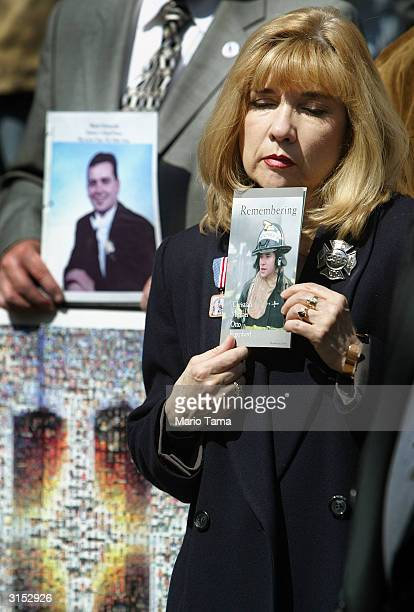 Sally Regenhard holds a photograph of her son Christian a firefighter who died in the World Trade Center attacks next to a photo of Mark Petrocelli...