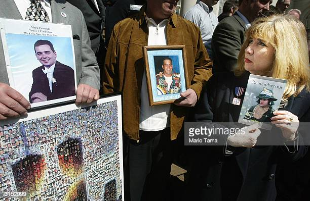 Sally Regenhard holds a photograph of her son Christian a firefighter who died in the World Trade Center attacks next to photos of Mark Petrocelli...