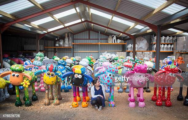 Sally Taylor from the Shaun in the City charity arts trail poses for a photograph with some of the Shaun the Sheep sculptures that have been created...