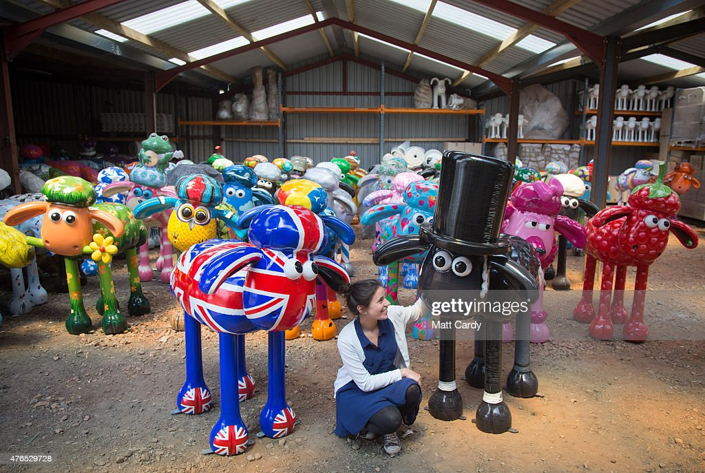 Sally Taylor from the Shaun in the City charity arts trail poses for a photograph with some of the Shaun the Sheep sculptures that have been created by artists, designers and celebrities ahead of their delivery to Bristol at their place of storage in a barn at a farm near Goldcliff on June 10, 2015 in Newport, Wales. From July 6 to August 31 the children's charity is bringing 70 Shaun the Sheep sculptures to green spaces across Bristol and later in the year the flock will go to auction with funds raised going to The Grand Appeal, the Bristol's children's hospital charity.