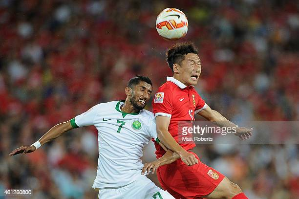 Salman AlFaraj of Saudi Arabia and Wu Xi of China PR compete for the ball during the 2015 Asian Cup match between Saudi Arabia and China PR at...