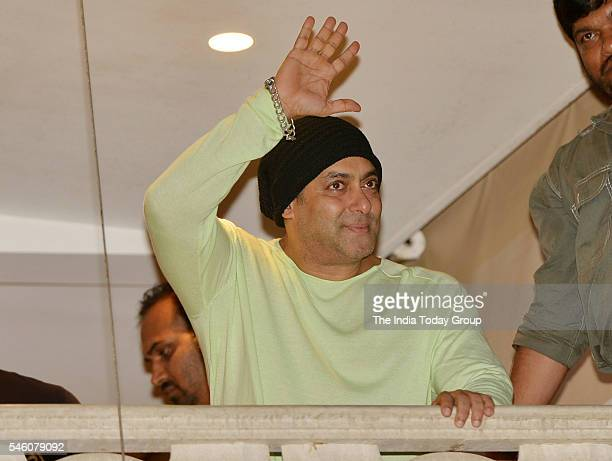 Salman Khan waves as he greets fans gathered outside his residence during the festival of Eid alFitr in Mumbai