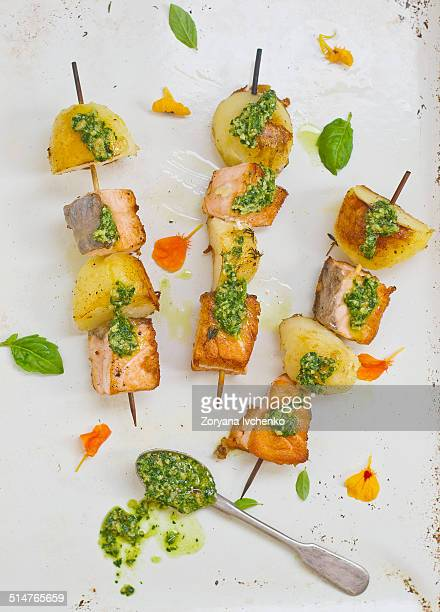Salmon and potatoes on sticks with pesto sauce
