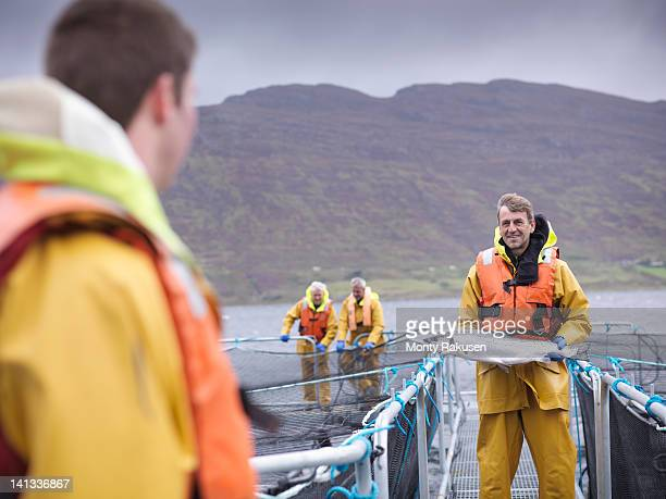 Salmon farmer holding hand reared Scottish salmon on farm pontoon on sea loch