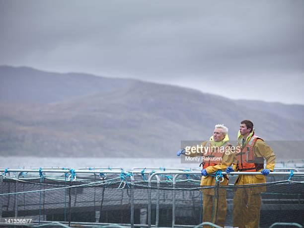 Salmon farmers on Scottish salmon farm pontoon