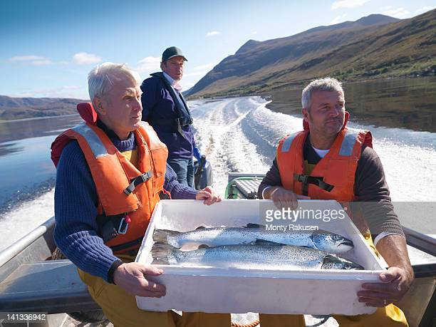 Salmon farmers travelling in fishing boat with box of freshly caught salmon