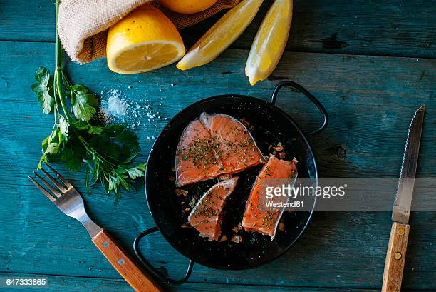 Salmon fillets on plate with parsley, lemon and salt