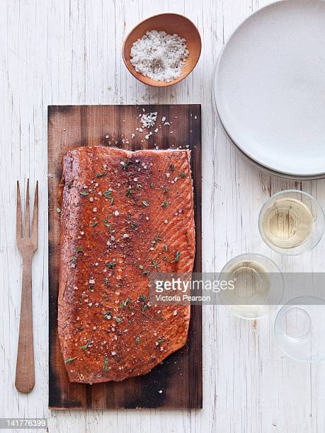 Salmon on a cedar plank served with white wine.